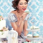 Beautiful lady is about to eat a cupcake at a tea party