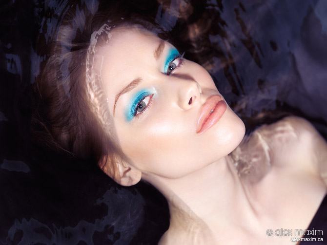 Sensual beauty portrait of a woman with blue makeup lying in wat