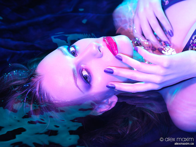 Beauty portrait of woman lying in water with purple makeup and m