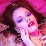 Beauty portrait of woman lying in water with makeup in vivid pup
